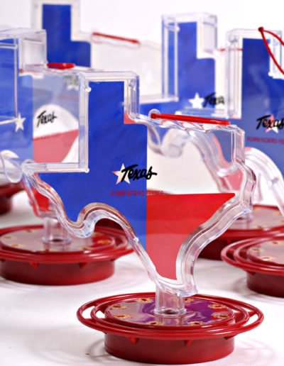 Item #108 – Texas Shaped 22 oz. easy fill plastic container. Guaranteed not to drip. Designed to feed ONLY hummingbirds. Red ABS Plastic base (non-metallic) Full ring perch with 8 feeding stations with metal hanger. Case Qty: 12